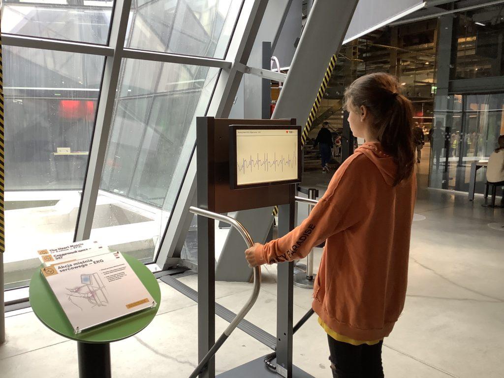 ポーランドのコペルニクス科学センターの取っ手を握って脈拍を測る装置を使う女の子