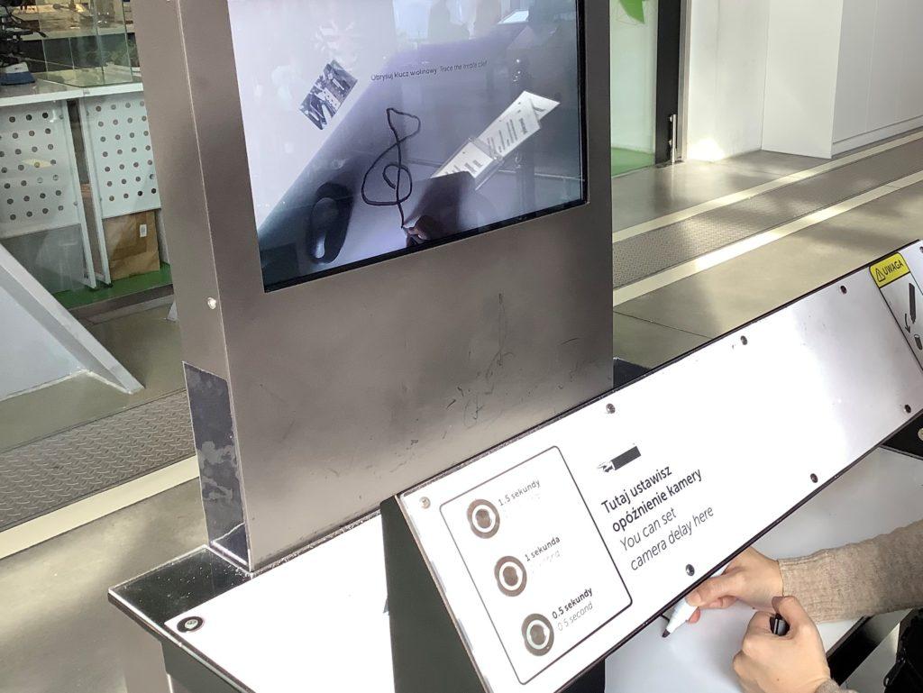 ポーランドのコペルニクス科学センターでモニター越しにト音記号を描く