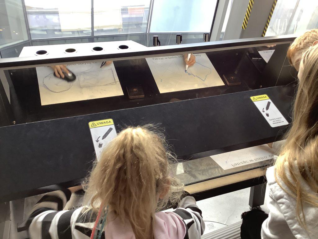ポーランドのコペルニクス科学センターで鏡越しに絵を描く女の子二人