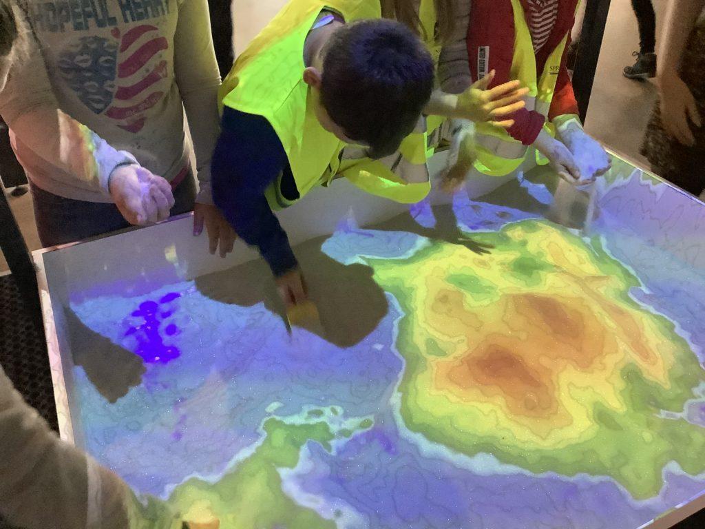 砂の盛り上がりで等高線が表示される装置で遊ぶ子どもたち