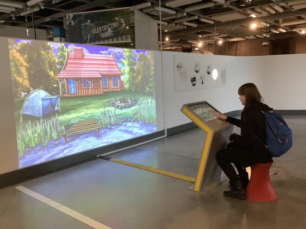 女の子が操作盤を使って、描いた家やテント、庭の絵がモニターに表示されている