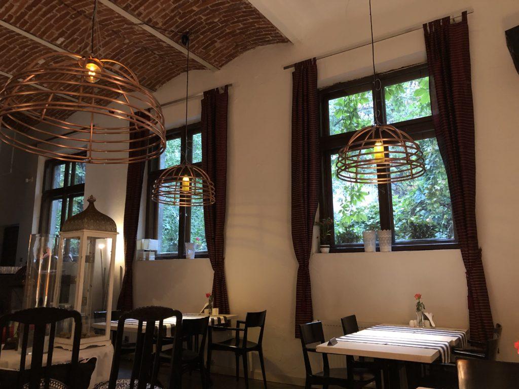 ポーランドのレストランの内装、レンガの天井、窓、照明、黒と白のテーブル