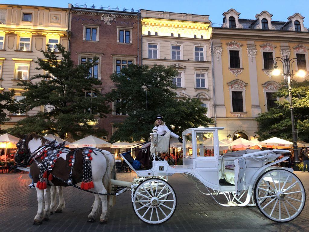 クラクフ旧市街の広場でお客を待つ白い馬車