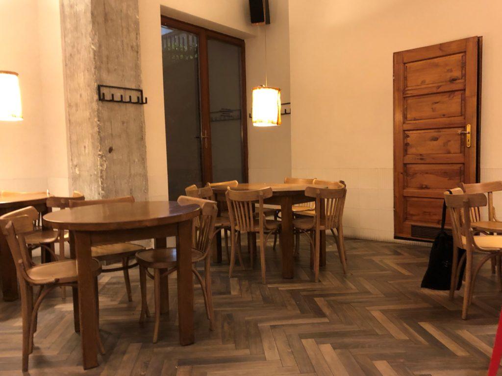 クラクフのカフェの木調の内観、丸テーブルと椅子