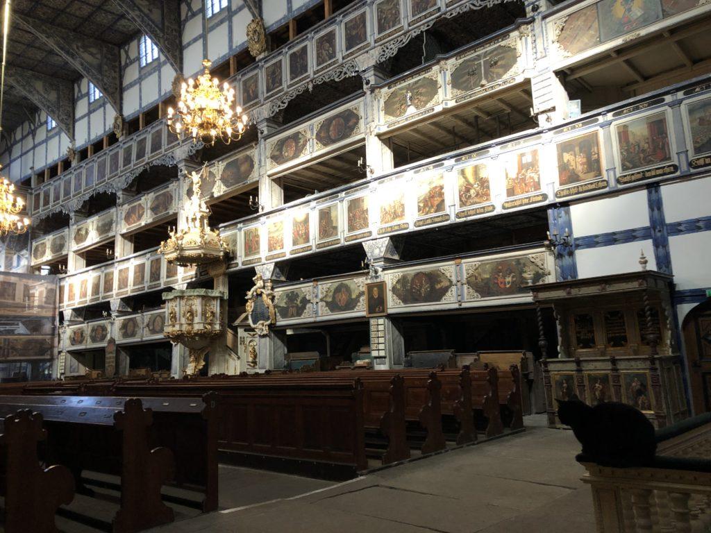 ポーランドのヤヴォル平和教会の内装と祭壇に座る黒猫