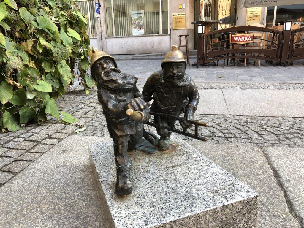 ヴロツワフの消防士2人の銅像ははしごとホースを持っている