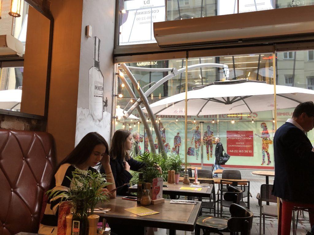カフェ、AïOLIの内装は大きな窓があり窓辺にお客さんが座っている