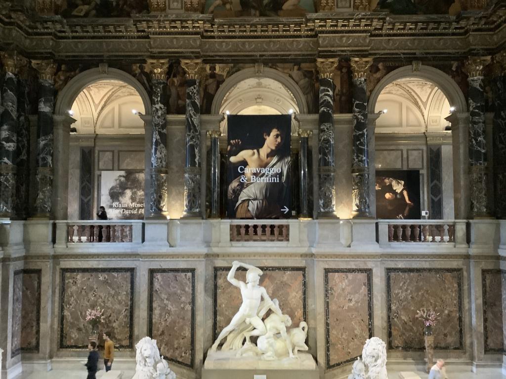 ウィーン美術史美術館の入り口付近の石像とカラヴァッジョのポスター