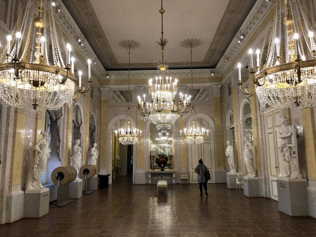 アルベルティーナ美術館のシャンデリアと石像が飾られたホール
