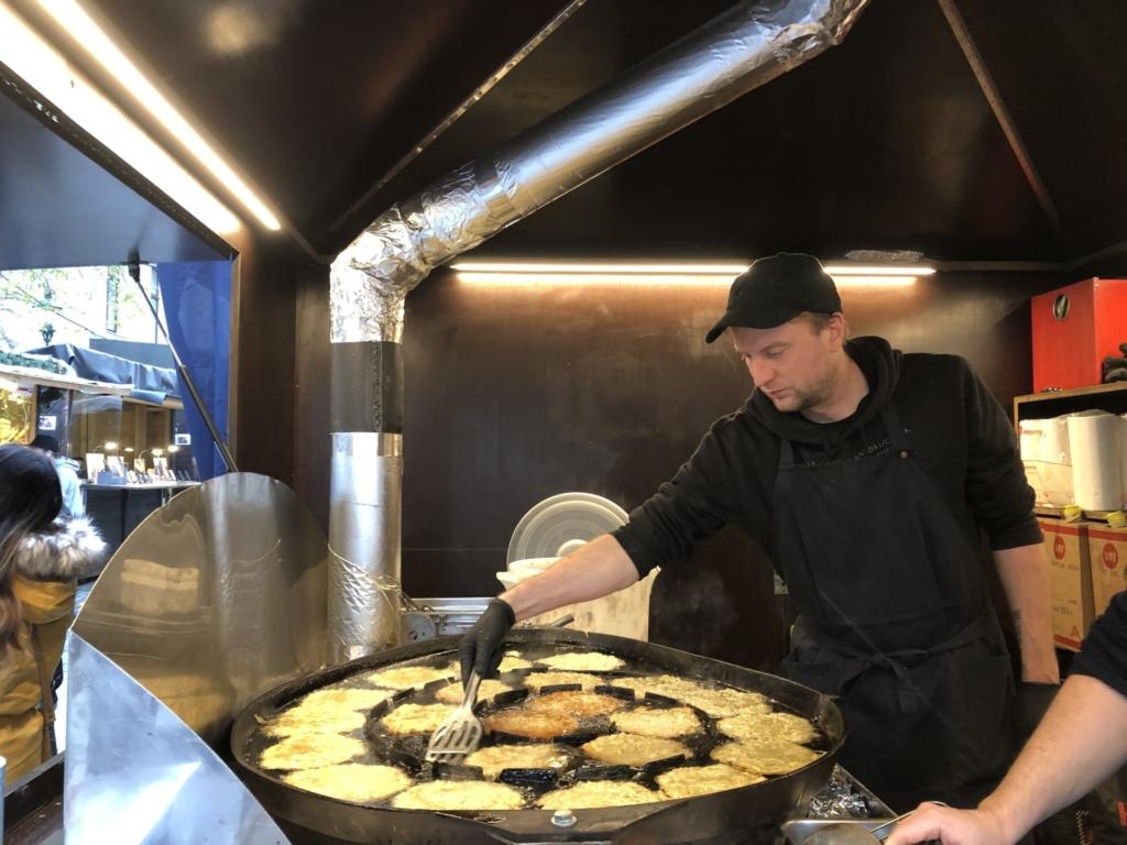ウィーンのポテトパンケーキの大鍋と揚げる男の人