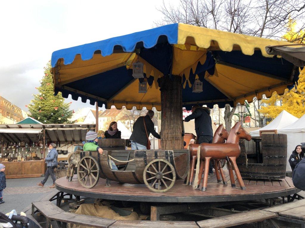 Siegburg(ジークブルク)クリスマスマーケットの手動のメリーゴーランドを回す男性