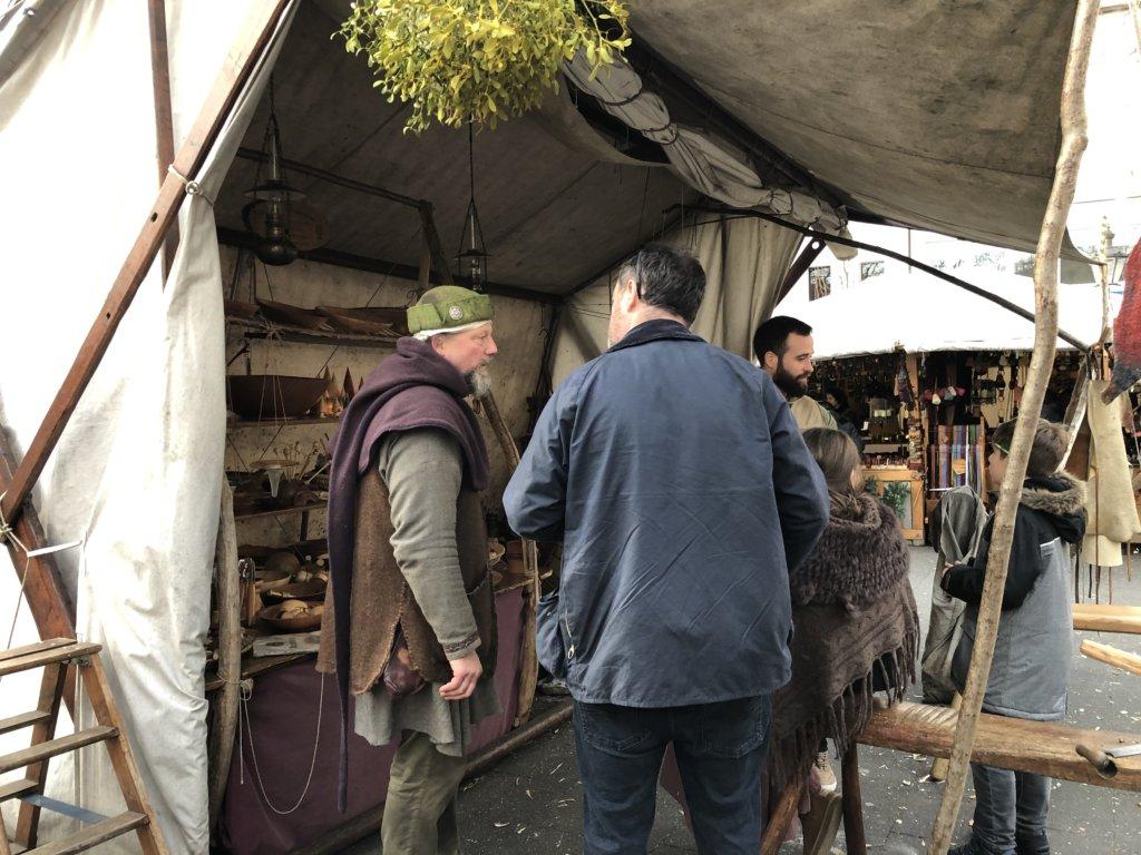 中世の格好でクリスマスマーケットで働く男性