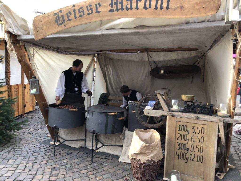 栗炒る大きな鍋と中世の格好で働く男性