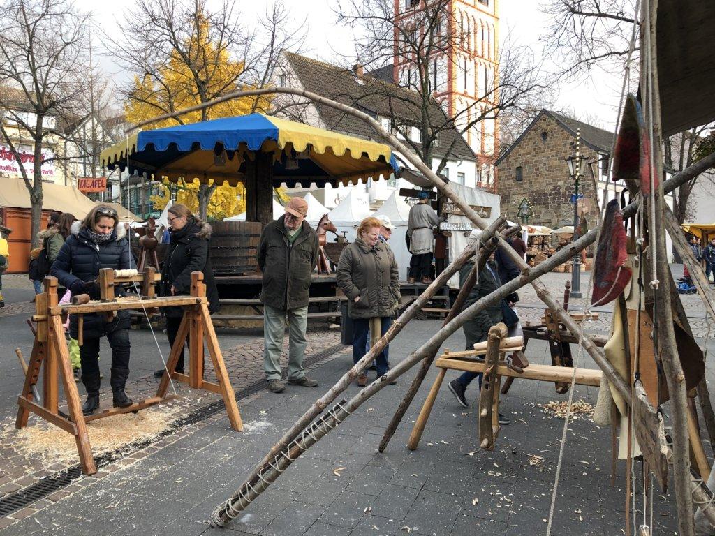 中世のクリスマスマーケットの木工屋で木を削る女性