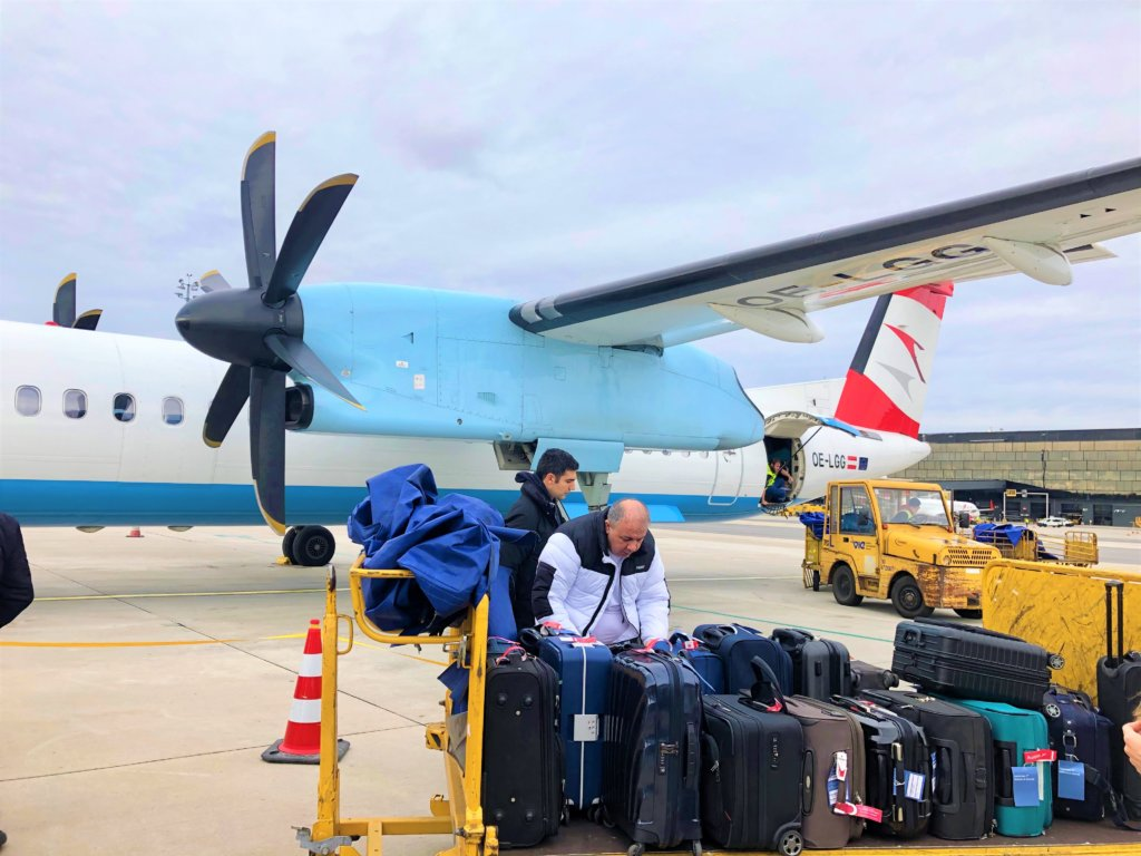飛行機と飛行場に並べられる手荷物