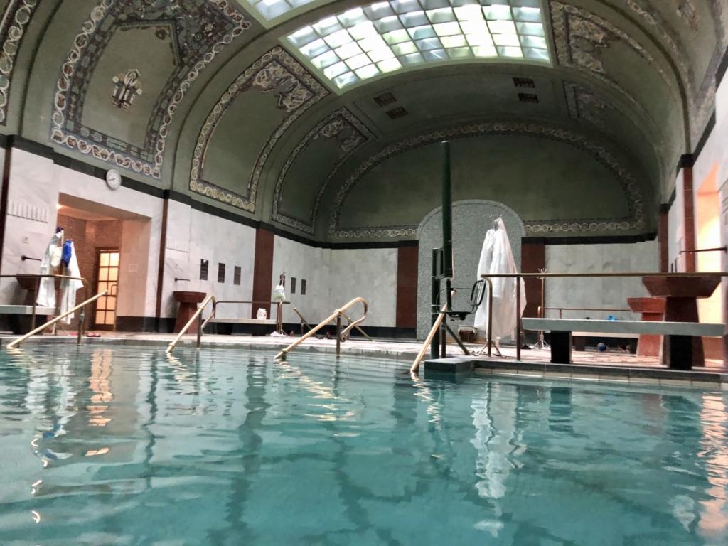ゲッレールト温泉Gellért Thermal Bathの温泉と緑のタイル画とベンチ