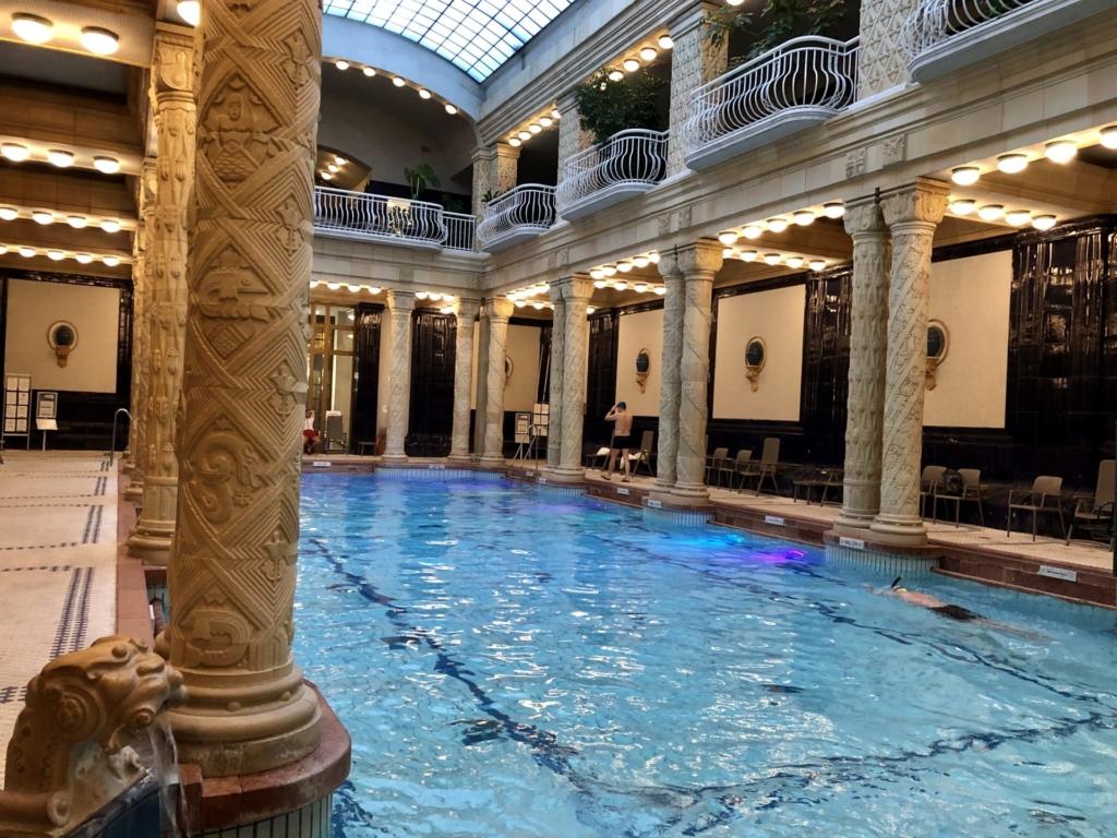 ゲッレールト温泉Gellért Thermal Bathの室内プールで泳ぐ人